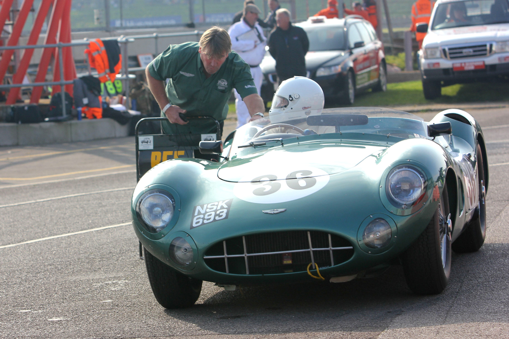 Chris Woodgate leans in to talk to Adrian Beecroft in the Aston Martin DBR1/300, a model which I must confess is my all time favourite sports racing car. I'm sure that in view of subsequent events Adrian probably feels that it would have been good if his race had ended here. Photo - Pat Arculus, Tripos Media