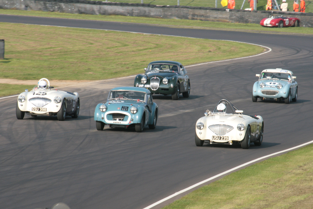 Three abreast. From left to right, Austin Healey team Captain, Nigel Grice, Wil Arif in Paul Ziller's Triumph TR2, and Katarina Kyvlova. Behind is Marc Gordon (XK150) and John Tewson in his Frogeye Sprite. Two of the 5 were not to reach this exit of Quarry next time round.  Note Jonathan Abecassis looking ruefully at his 'parked' Austin Healey, in the background.                        Photo - John Turner