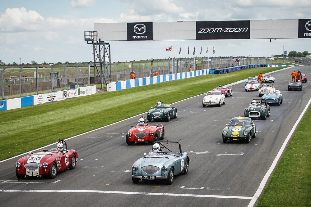The grid lines up ready for the green flag lap. You will note the absence of Keith Hampson's Sunbeam Alpine Le Mans from the grid and the tell tale smoke emerging from the back of Mike Freeman's Lotus Elite.   Story below                        Photo - Chris Dicken, Tripos Media