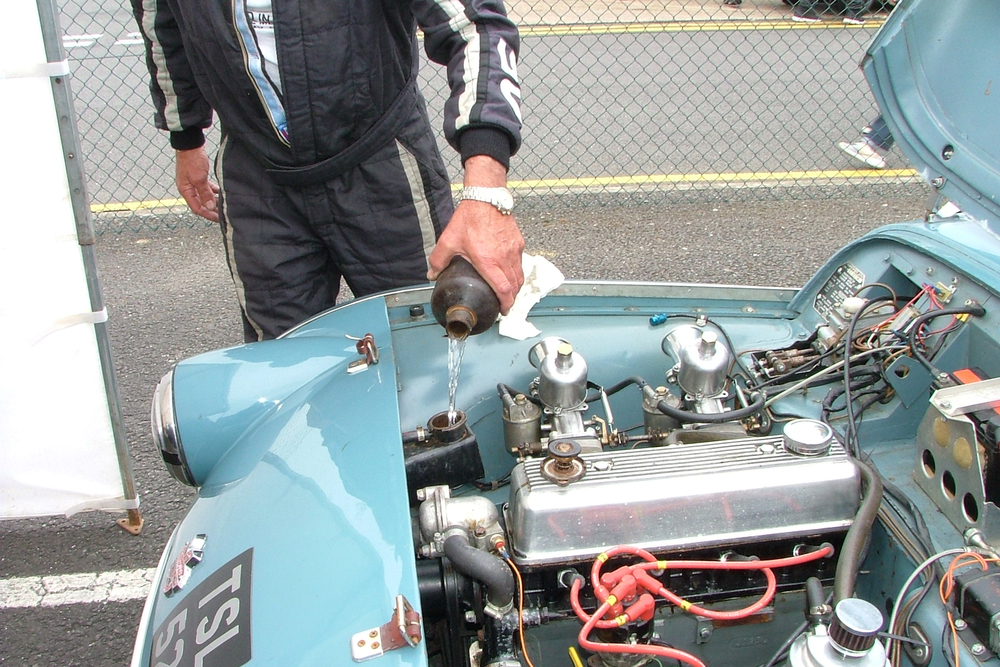 Paul Ziller tops up the header tank on the TR2. It allowed him to complete 4 laps before retiring                Photo - John Turner