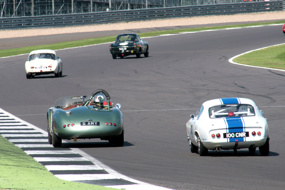 Towards the back, Keith Hampson (Sunbeam Alpine Le Mans) making good forward progress from his enforced low starting position leads Simon Gurney (MGA), Chris Guest (RGS Atalanta) and Nick Atkins ( Lotus Elite)  heading through Woodcote.   Photo - John Turner