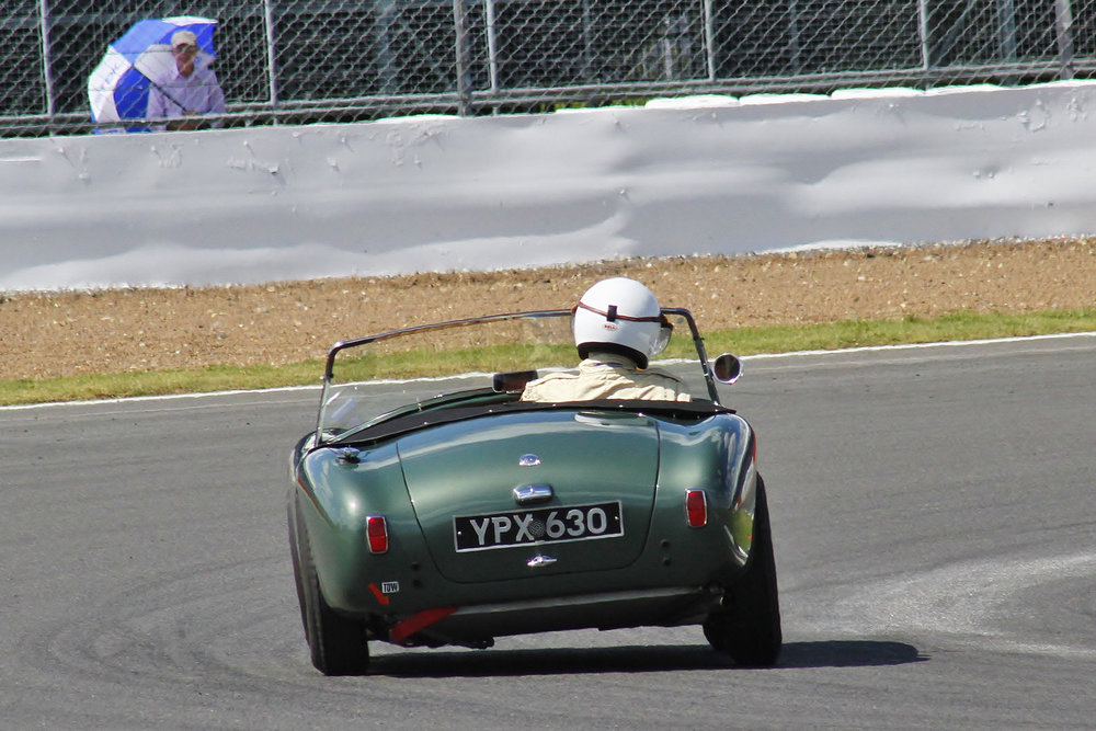 David Bennett about to head through Woodcote. The solitary spectator with sun shade at this point adds a certain artistic posterlike quality  Photo - Bob Bull, Tripos Media