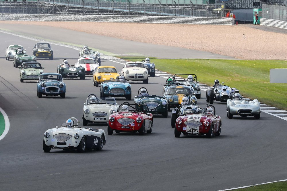 The first nine cars are already through but a splendid chasing group of cars followed. Note Jonathan Abecassis (20) has dropped back but had started to recover by the end of the lap. I'm minded to call the pack of Healeys an Ostentation of Austin Healeys but a tad contived maybe. Note the very prominent green helmet of Martin Stretton in David Graus Frazer Nash Targa Florio.   Photo - Richard Styles