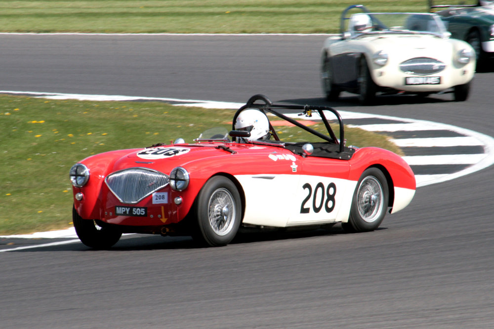Paul Mortimer, first time out with us in his Austin Healey 100M ahead of Austin Kinsella in the 100S, through Luffield for the second time  Photo - John Turner