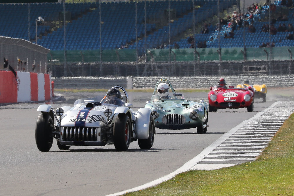 The first car to be lapped by the leader was the little Kieft Climax of Craig McWilliam and he is about to suffer the same fate from the Maserati and Ferrari                                                                                                                            Photo - Richard Styles