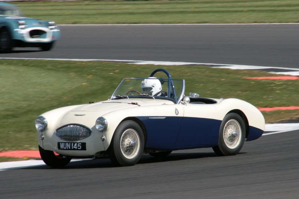 Austin Kinsella in John Briggs Austin Healey 100S. Note that the visual distinguishing feature that sets it apart from the 100/4 & 100M models is the narrower and more symmetrical radiator aperture.  You will also note the apparent absence of competition numbers. In fact the number (106) was mounted on bonnet and bootlid so that it could be seen from the air!!                       Photo - John Turner