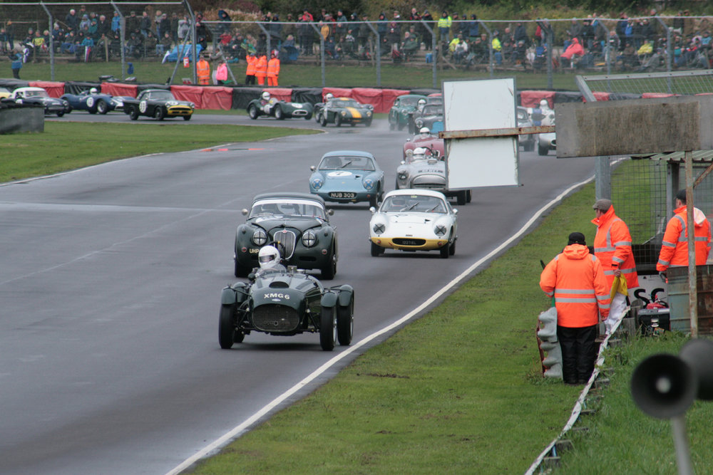 The pack charges through Quarry as a great start sees Martyn Corfield in his Frazer Nash Le Mans Replica lead and heading down Farm Straight and under the marshal's board towards the Esses for the first time. Marc Gordon (Jaguar XK 150) and Robin Ellis (Lotus Elite) give chase.  Photo - John Turner