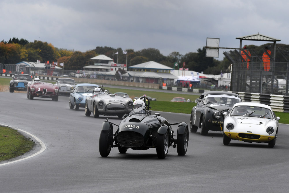 Superb start by Martyn Corfield in the FNLMR saw him head the field into Quarry, chased by Poleman, Robin Ellis (Lotus Elite) and Marc Gordon (Jaguar XK150) . Front row man, Andy Shepherd (AC Ace) is 4th, whilst Brian Arculus (Lotus Elite) and Chris Mann (Alfa Romeo Disco Volante) made good starts to be 5th and 6th respectively. Note however, cresting the rise in the Metallic grey Aston Martin is Tim Stamper up from 16th on the grid. Stephen Bond's Lister Bristol is all but hidden behind the Alfa.  Photo - Jeff Bloxham