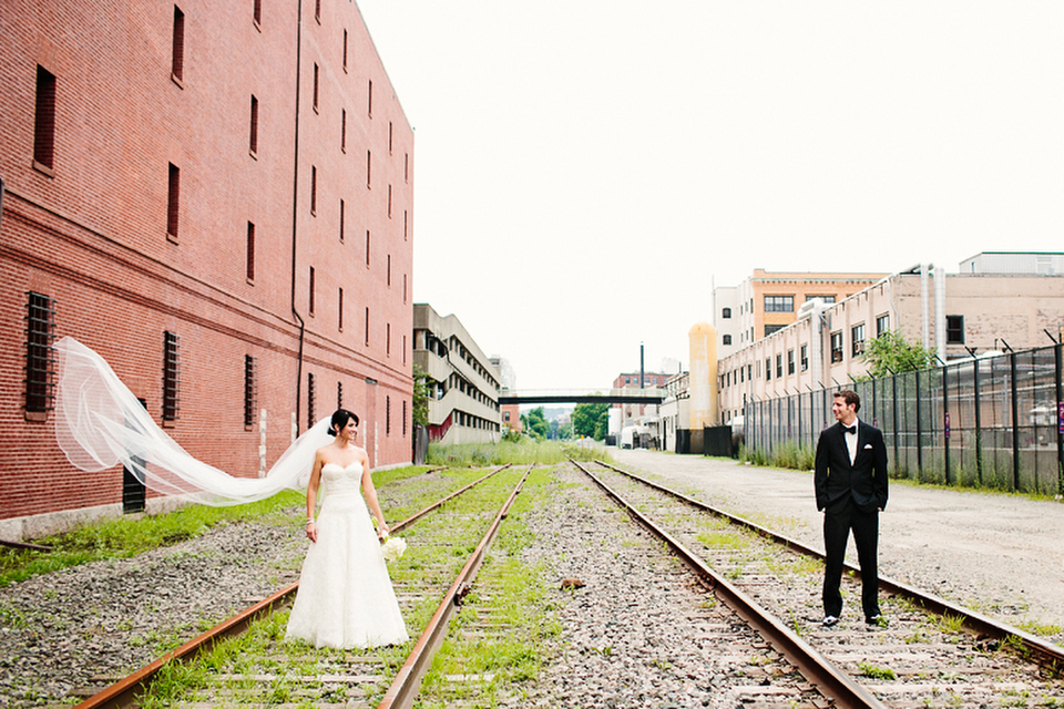Outdoor wedding portrait on Boston train tracks with bridal veil flowing in the wind.