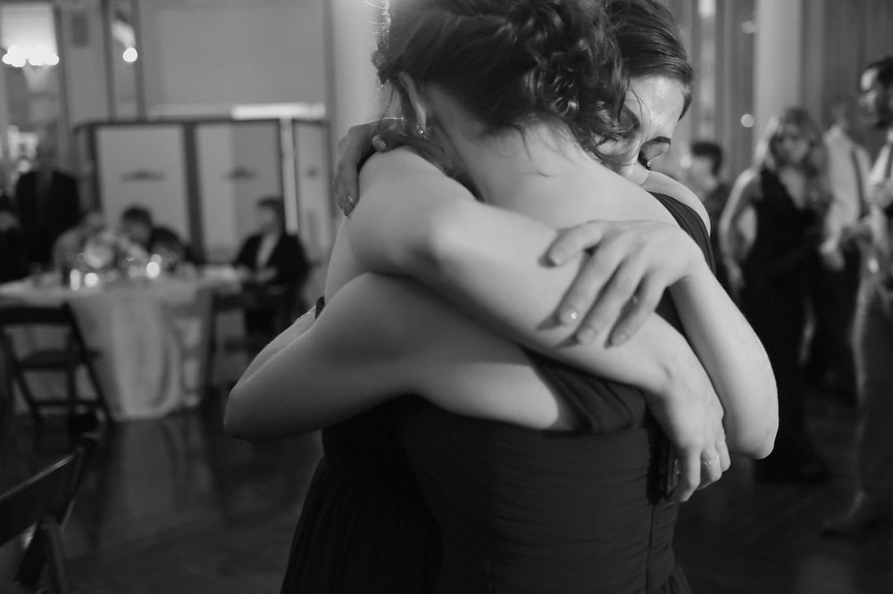 two women hug at wedding at canfield casino in saratoga springs, ny