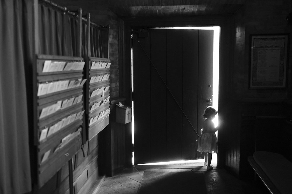 flower girl peeking out the door in stockbridge wedding in western massachusetts