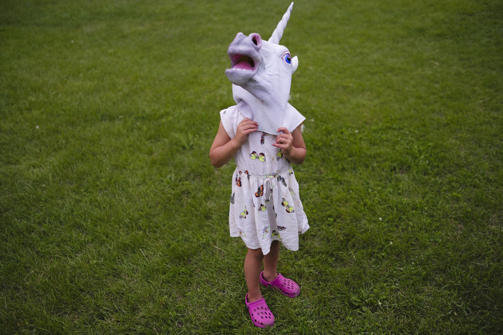 child in unicorn mask at path of life sculpture garden in windsor vermont