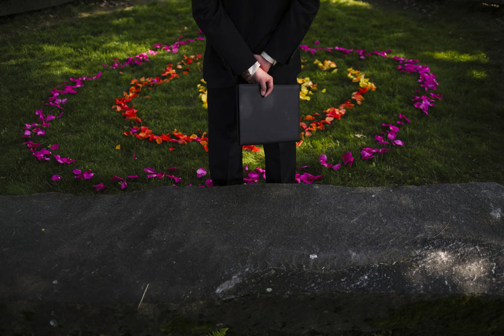 officiant overlooks the ceremony venue at path of life sculpture gardens in windsor vermont before it begins