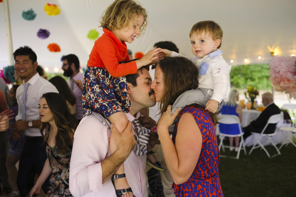 guests steal kiss with kids on their shoulders at kid-friendly vermont wedding
