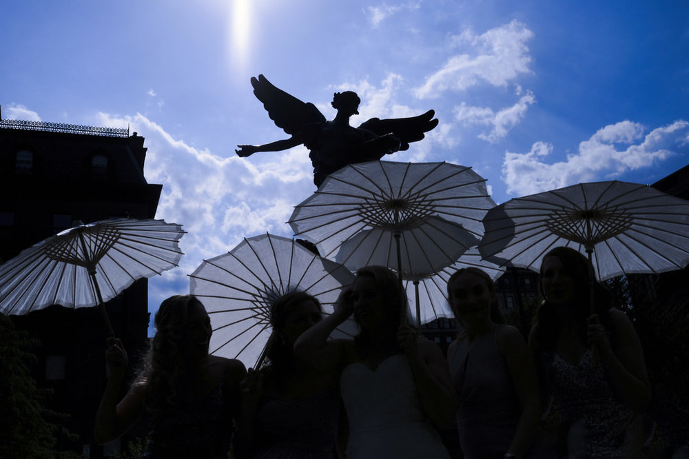 Umbrellas and angel statue on the way to the ritz carlton hotel in boston for a wedding