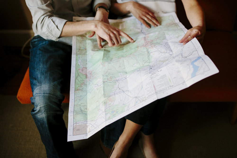 engaged couple looks at map before engagement shoot in belmont