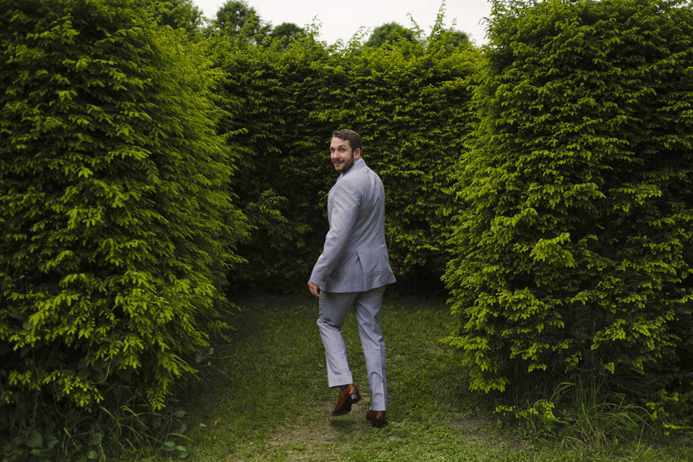 The groom enters labyrinth made of shrubbery at the path of life sculpture garden for osme unusual bride and groom portraits