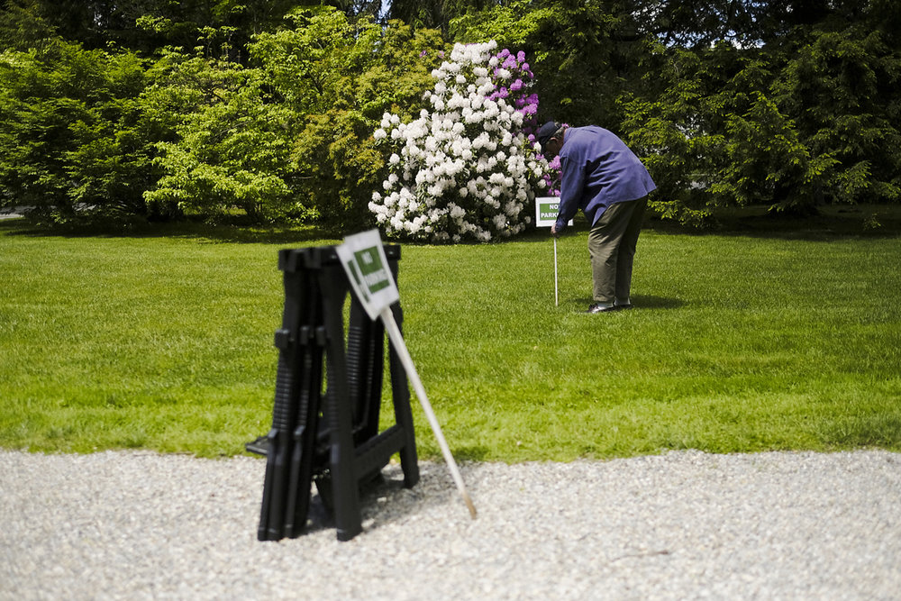 man helps put up signs at stockbridge tented wedding in the berkshires