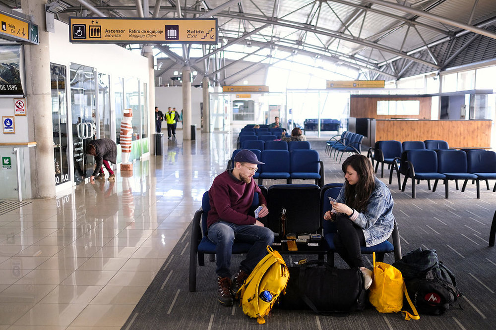 playing cards at the airport after elopement wedding in patagonia, chile