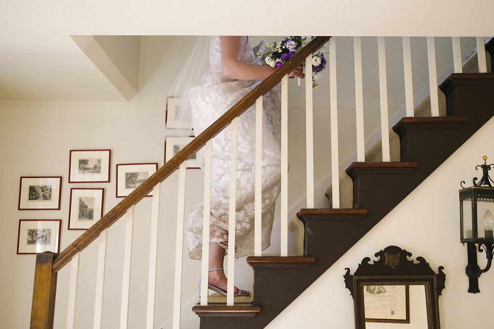 bride walking upstairs holding dress and flowers in stockbridge, ma