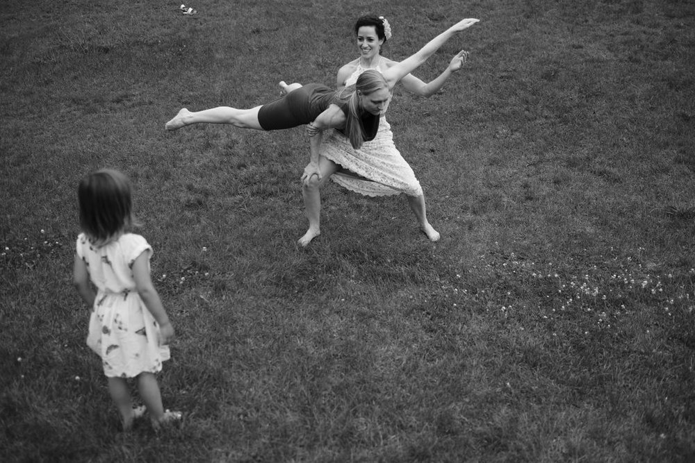 girl watches bride and friend do acrobatics at path of life sculpture garden in vermont