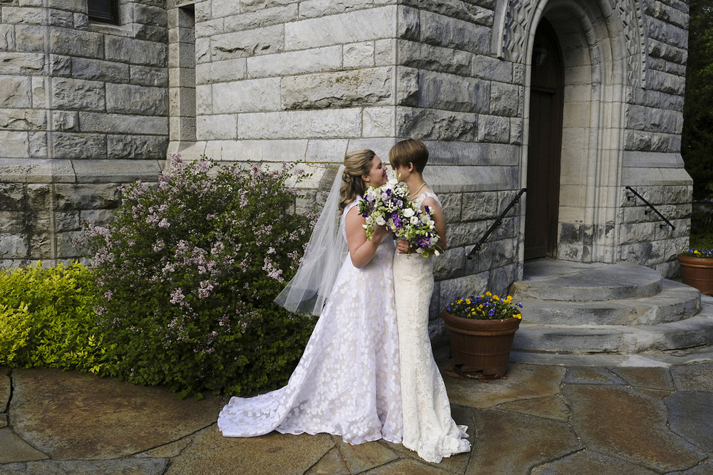 newlywed brides share a moment outside of church in stockbridge, ma