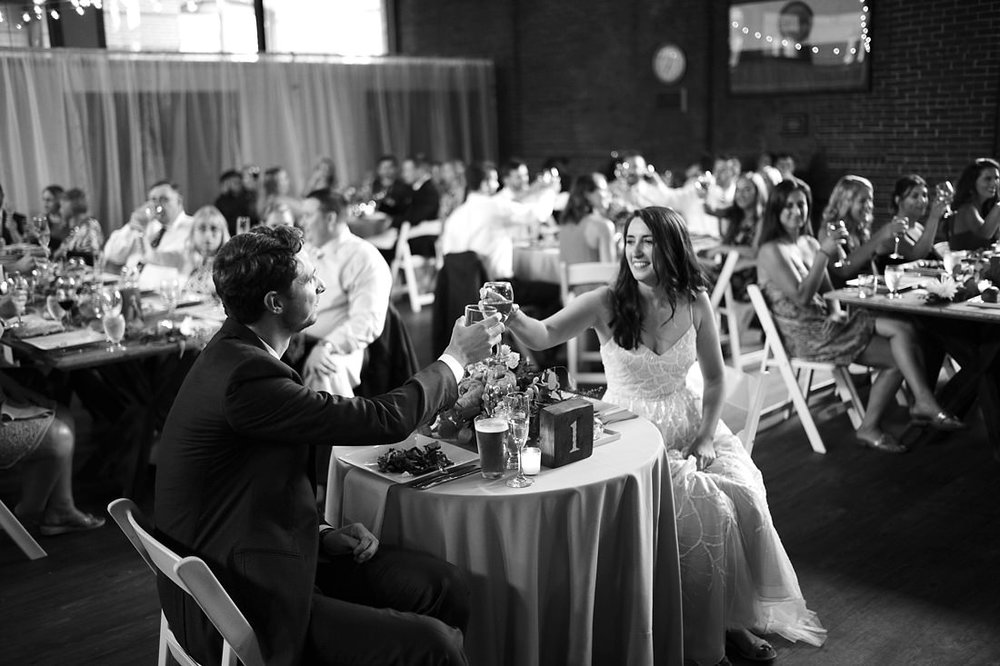 bride and groom cheersing at reception at the charles river museum of industry and innovation in waltham