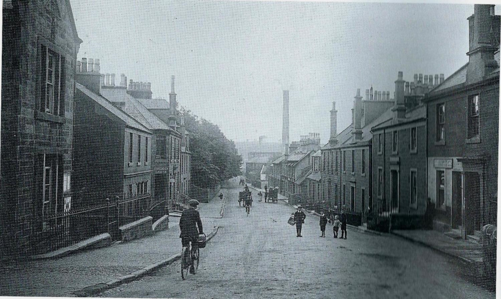 Dalry Ayrshire, New Street, the principle street, begins at Biggart's Mill, seen in the distance and ends at the Cross.