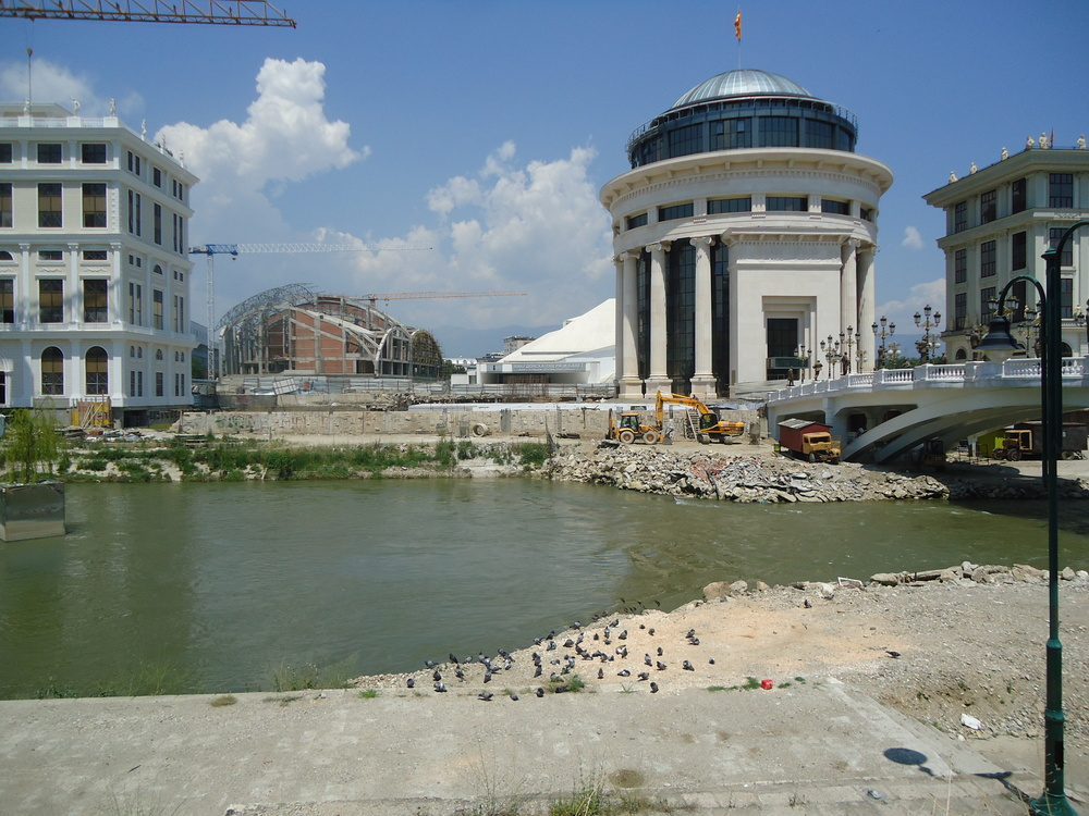 Skopje in 2013. Although the photograph is taken from a wider angle, the small while Modernist building in the center is the Opera House, which is currently dwarfed by the new Neoclassical constructions.