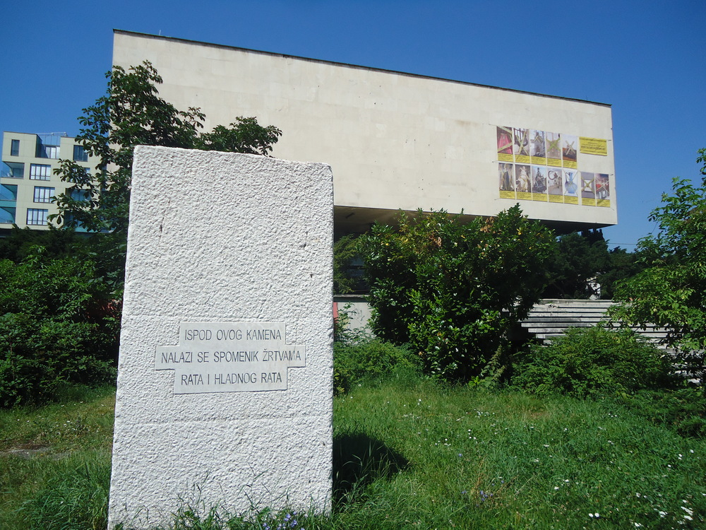Public Sculpture by Braco Dimintrijevic The inscription reads: The inscription reads: Under this stone there is a monument to the victims of the war and Cold War Behind it, the Museum of Revolution: still open for business