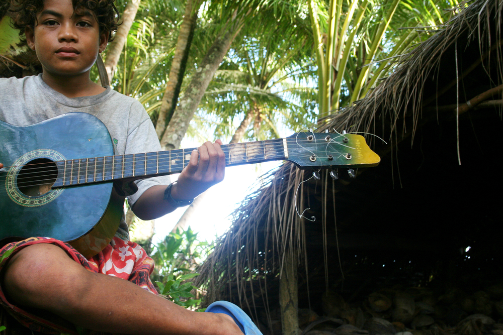 A kid with a guitar on the island of Wotegai. Yapese music tends to sound like traditional Hawaiian music.