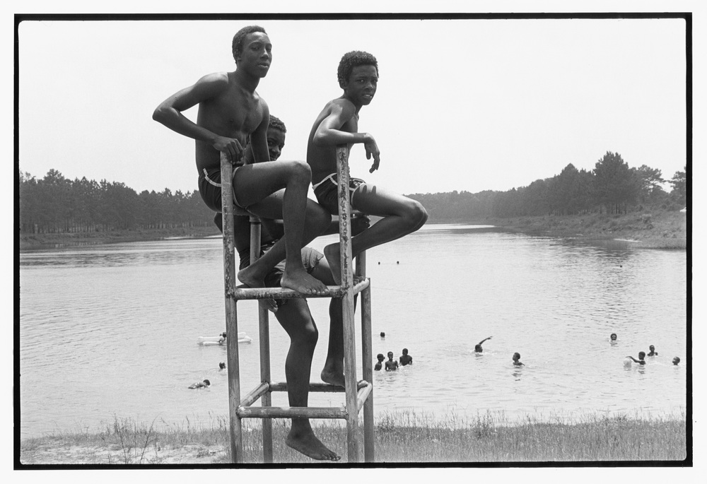 Three boys on lifeguard stand and swimmers, boat basin, 1979 June