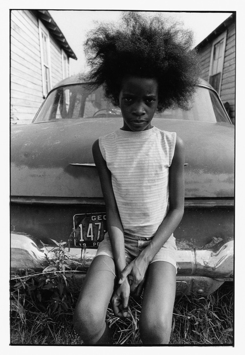 Girl with Afro sitting on bumper of old car, 1970