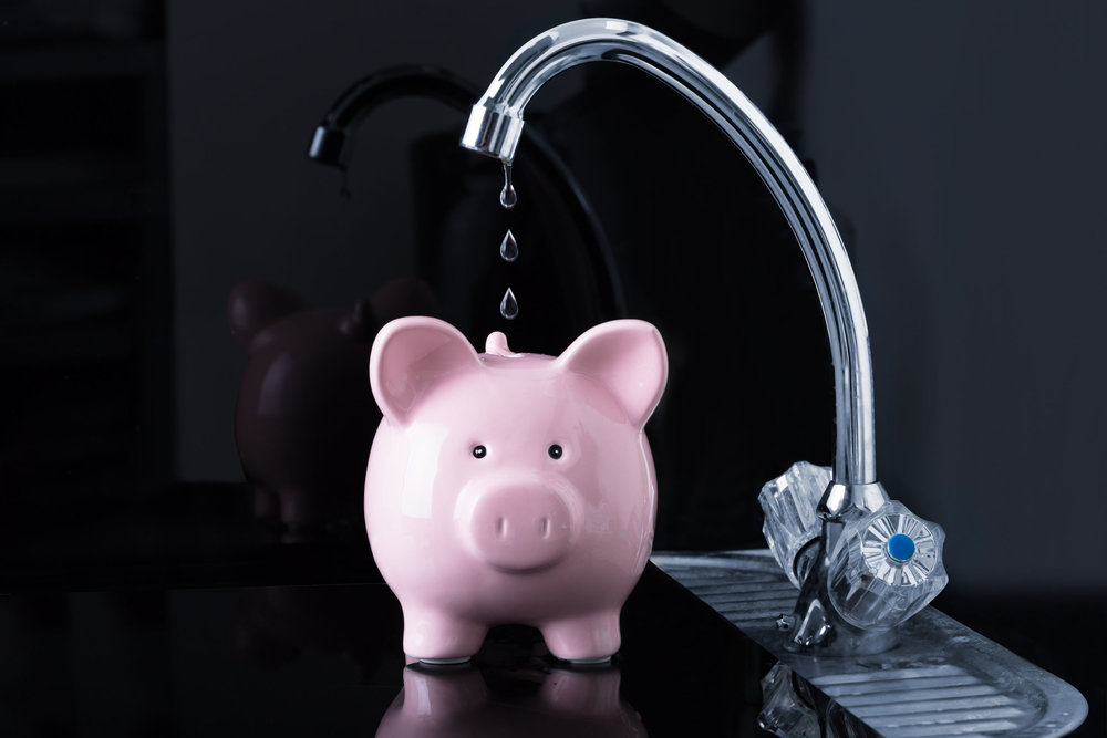 94716985 - dripping water droplets are falling in the pink piggybank from kitchen sink faucet