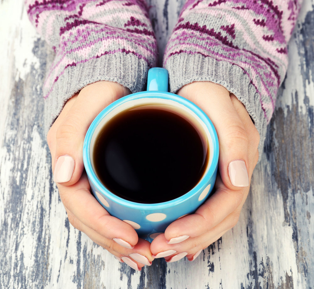 41576409 - female hands holding cup of coffee on wooden background