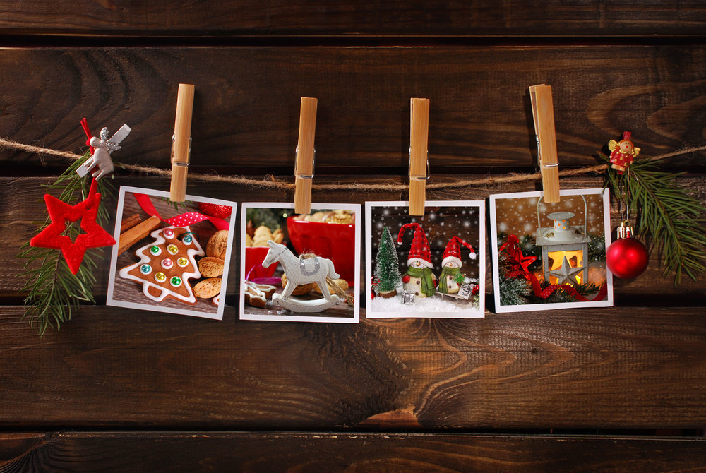 34365824 - four christmas  photos hanging on rope with bamboo clothespins against old wooden background