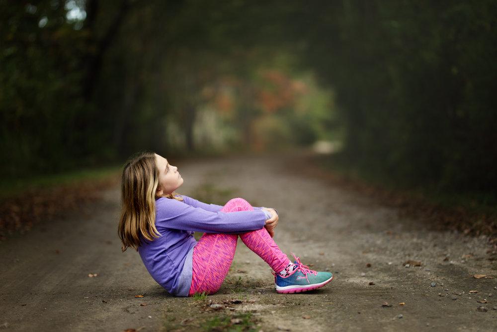 Girl sitting in road