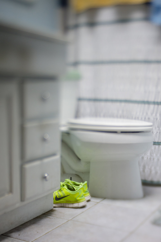 Nike running shoes on floor in bathroom
