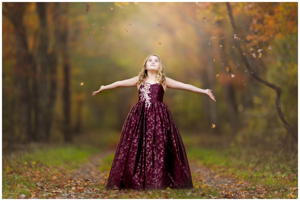 girl throwing leaves in the woods in South Kingstown, RI