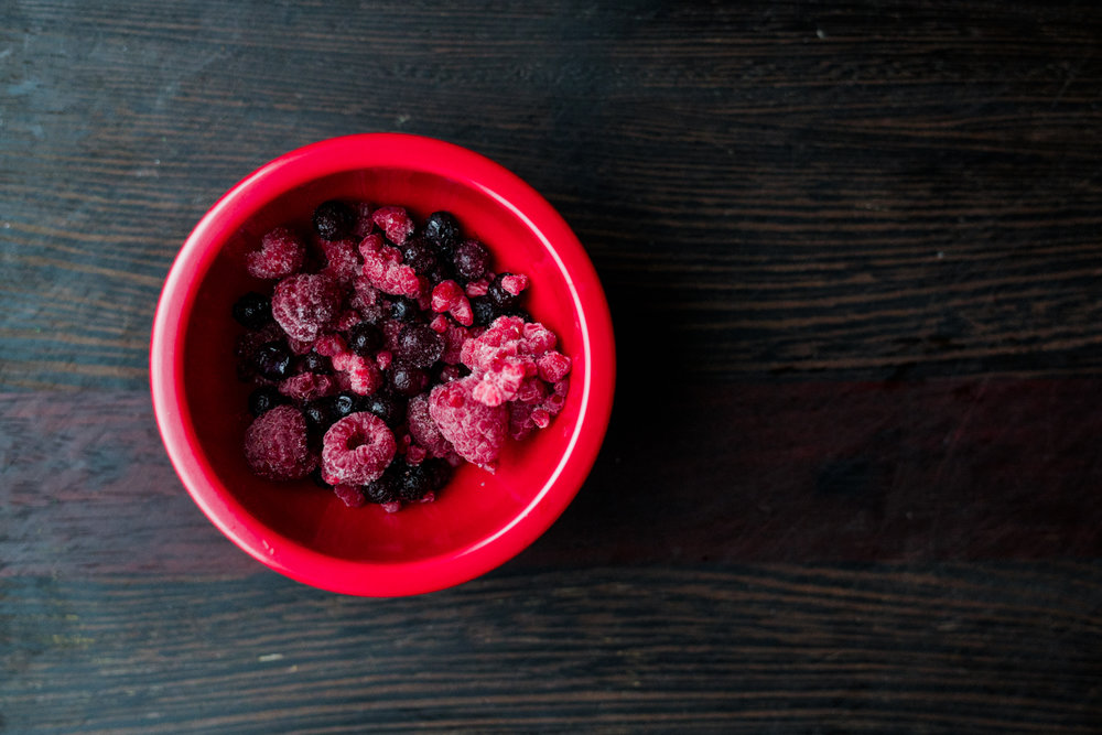Frozen raspberries and blueberries in a red bowl