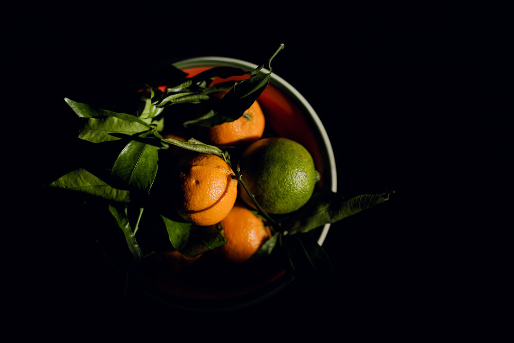 oranges and lime in a bowl