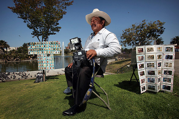 """Javier Prado sits in his folding chair waiting for customers at MacArthur Park. Photographers such as Prado, with their old-fashioned Polaroid cameras, have been fixtures in the area for nearly 40 years. "" - from LA Times article ""MacArthur Park's Polaroid portraitists are fading away"""