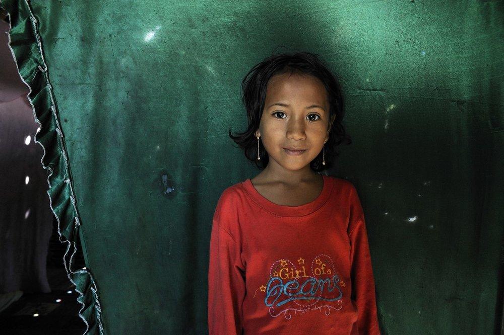 COA-by-Thijs-2  Dit meisje fotografeerde ik op het eiland Rinca, in het oosten van Indonesië. Rinca en het naastgelegen Komodo zijn bekend omdat het de enige plaatsen op de wereld zijn waar de Komodo varaan leeft; de grootste hagedis van de wereld. Voor toeristen vormen ze een bezienswaardigheid en dat is de reden dat er hier heel regelmatig groepen toeristen op bezoek komen. Toch voelt dit als een zeer afgelegen plek die nauwelijks aangeraakt wordt door de snelle veranderingen die ons leven kenmerken; het leven in de kleine dorpjes hier is er in de afgelopen decennia nauwelijks veranderd.