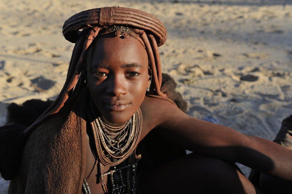 COA-by-Thijs-6  Ik reis elk jaar ruim twee maanden met een 4WD door het afgelegen en vrijwel onbewoonde noordwesten van Namibië. De mensen die ik daar nog tegenkom zijn vrijwel allemaal himba: één van de laatste nog echt nomadisch levende volkeren van de wereld. Prachtige, pure en onverschrokken mensen. Als ik mijn kamp opsla in de buurt van een nederzetting, komen de himba vaak pas 's morgens kennismaken; het is duidelijk een gewoonte om elkaar 's avonds met rust te laten. Dat gebeurde ook met dit beeldschone meisje, dat 's ochtends samen met een vriendin thee dronk bij mijn kampvuur.