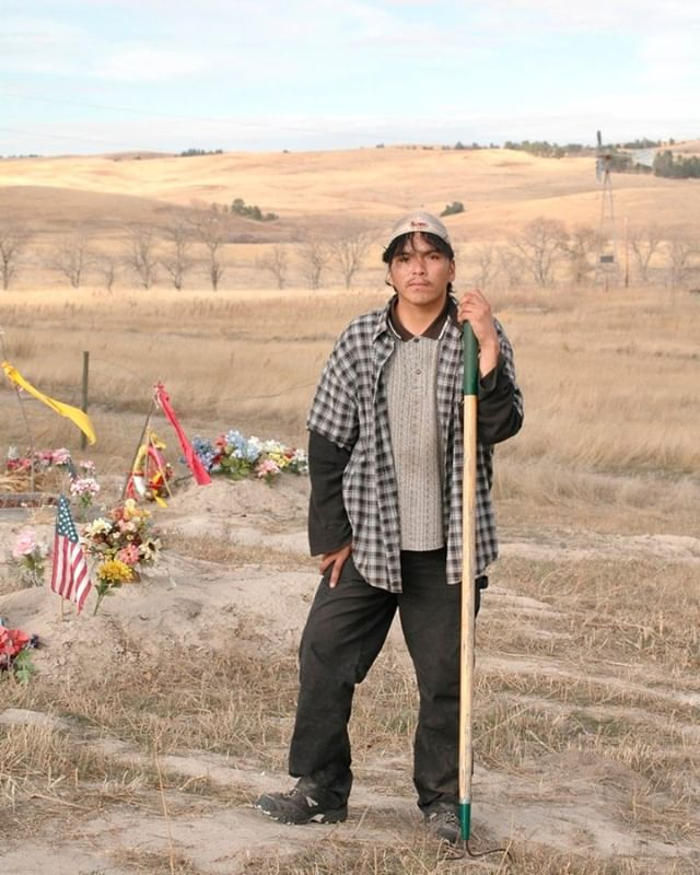 Wounded Knee, SD, United States  Aloysius Little Moon (26) is the sad-looking groundskeeper of the beautifully located #cemetery near the site of Wounded Knee. At least that's what he tells me.  My guess is that he's not actually a groundskeeper at all, but is only pretending to be one to score tips from the few tourists that visit this place. I wouldn't be surprised, as South Dakota's Pine Ridge Indian Reservation is one of the poorest places to live in the United States, with an estimated 80% of the adult population being alcoholic. Aloysius was willing to pose for my camera, but afterwards he asked me for 25 dollars to buy groceries.  From my book 'Men at work'  #woundedknee #massacre #southdakota #unitedstates #indigenouspeople #indianreservation #pineridgereservation