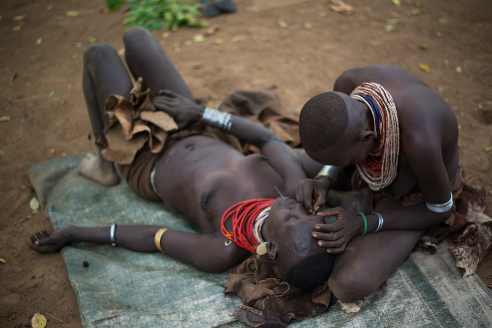An intimate task, women sometimes pluck each other's eyelashes.