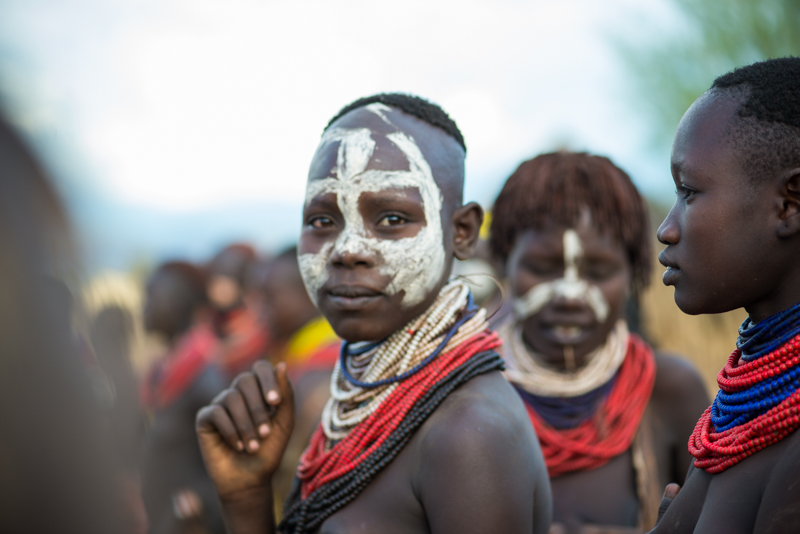 Men and women paint their bodies for a gathering.