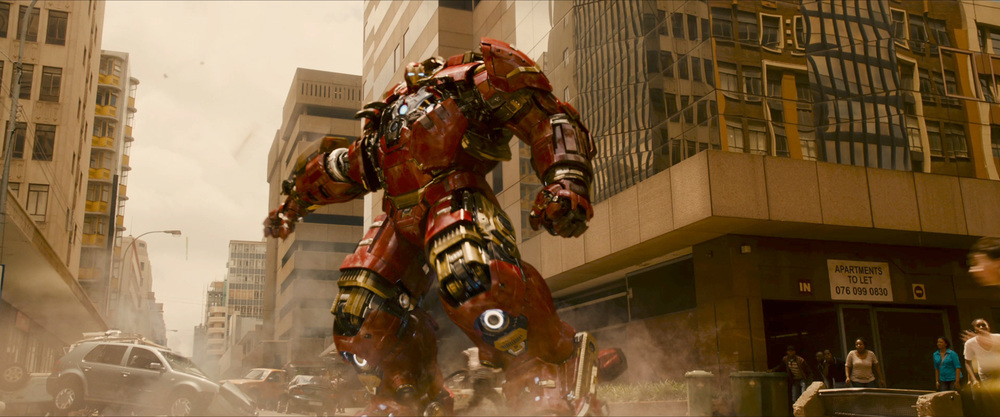 There is a blur over the left side of the Hulkbuster, it's a piece flying onto the suit. I'm guessing the Hulkbuster assembles around the Iron Man armor, in the same way the Mark 42 was a jumble of flying components that assembled onto Stark.
