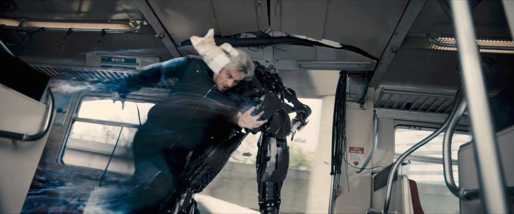 Quicksilver putting his shoulder into Ultron. Asian writing on the pillar and signs.