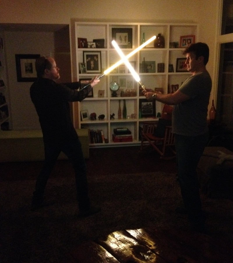 photo-of-joss-whedon-and-nathan-fillion-locked-in-lightsaber-duel